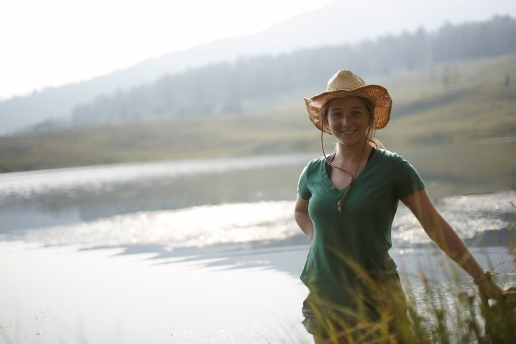Stock Photo: 1838-14165 Smiling Young Woman With Lake in Background