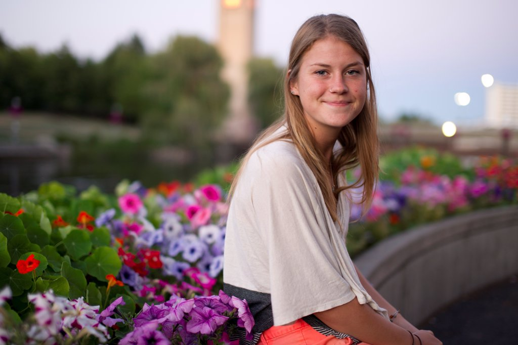 Stock Photo: 1838-14183 Smiling Young Woman Sitting Near Flowers