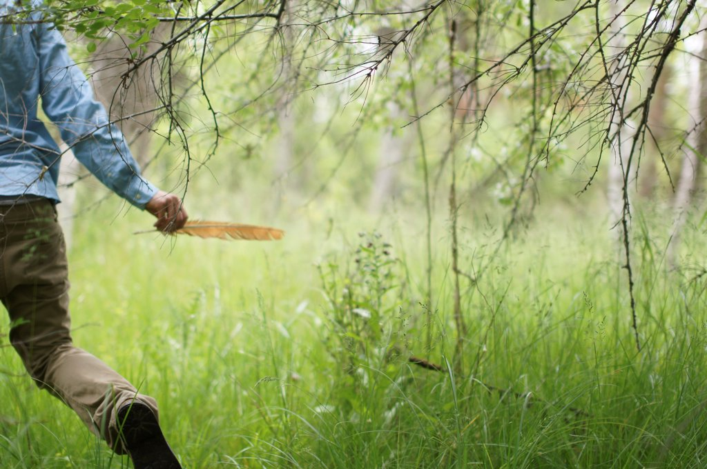 Man Running in Woods With Feather in Hand : Stock Photo