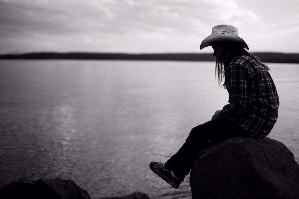 Stock Photo: 1838-14191 Young Woman in Cowboy hat Sitting on Rock Near Lake, Yellowstone National Park, USA