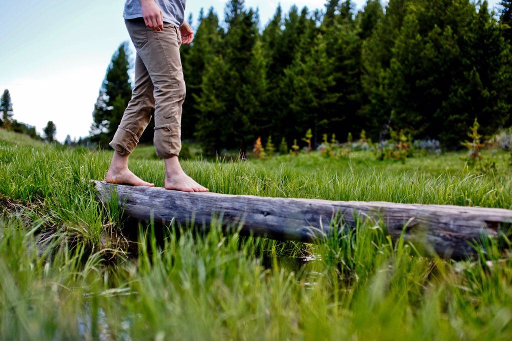 Stock Photo: 1838-14193 Young Man Crossing Log Barefoot