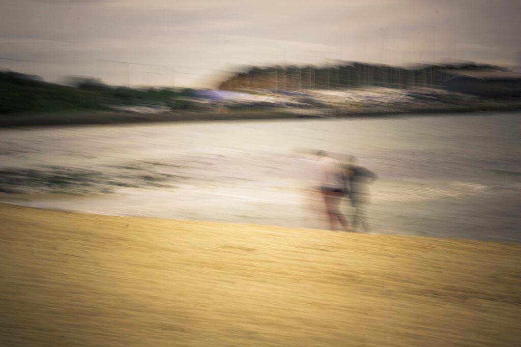 Blurred Couple Walking Along Beach : Stock Photo