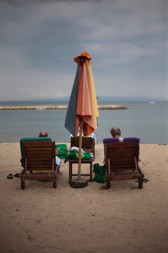 Stock Photo: 1838-14281 Two Men Relaxing on Lounge Chairs on Beach, Rear View, Bali, Indonesia