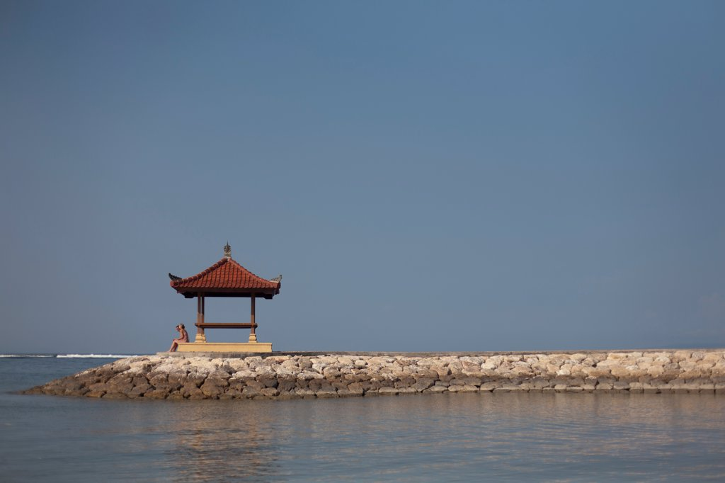 Two People Sitting Next to Traditional Pavilion at End of Jetty, Bali, Indonesia : Stock Photo