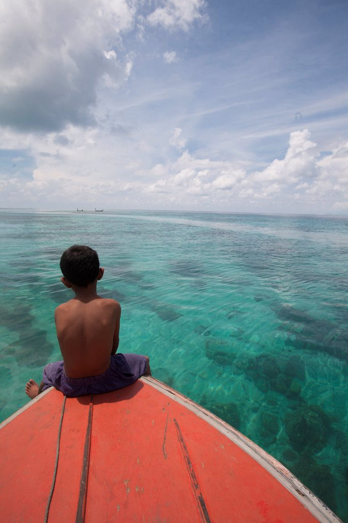 Young Boy Sitting at Front of Boat and Looking out to Sea, Borneo : Stock Photo