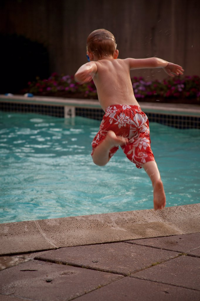 Stock Photo: 1838-14334 Young Boy Jumping into Swimming Pool