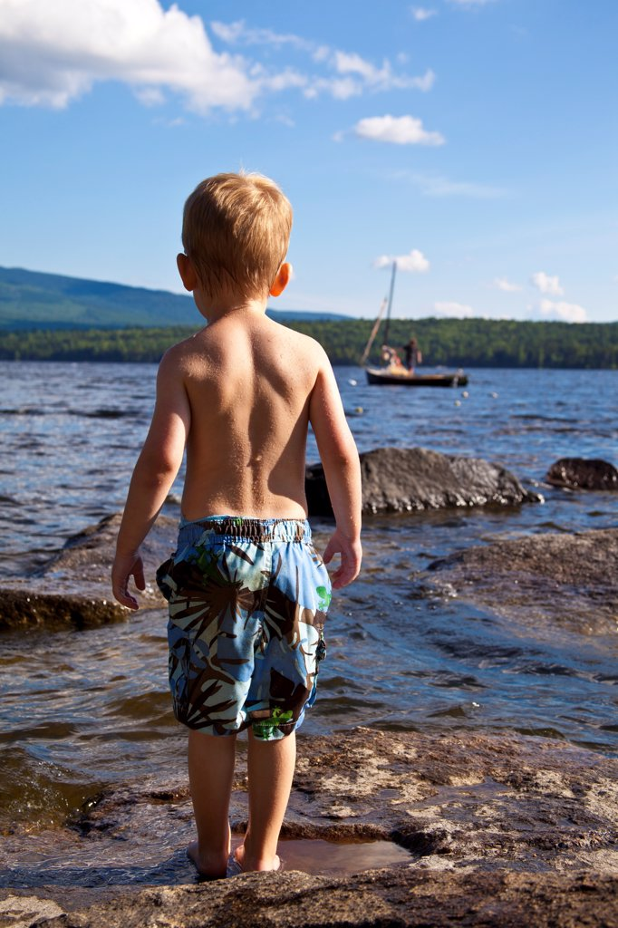 Stock Photo: 1838-14347 Young Boy in Bathing Suit Standing on Rocks at Water's Edge