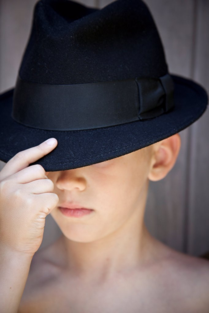 Young Boy Touching Brim of Fedora Hat : Stock Photo