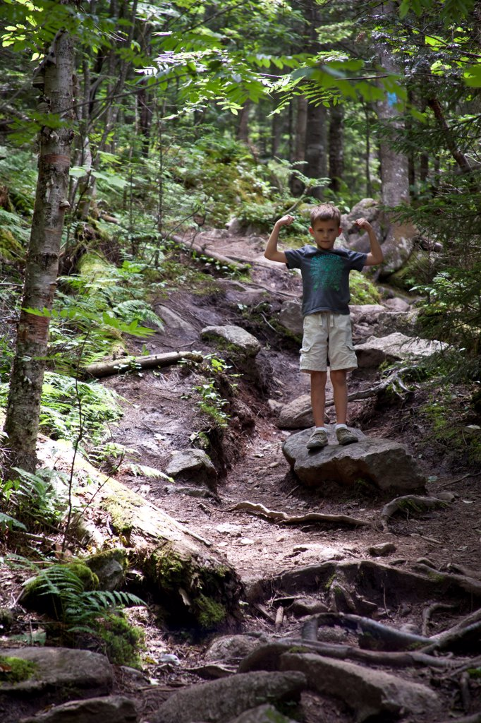 Young Boy Flexing Arm Muscles on Path in Woods : Stock Photo