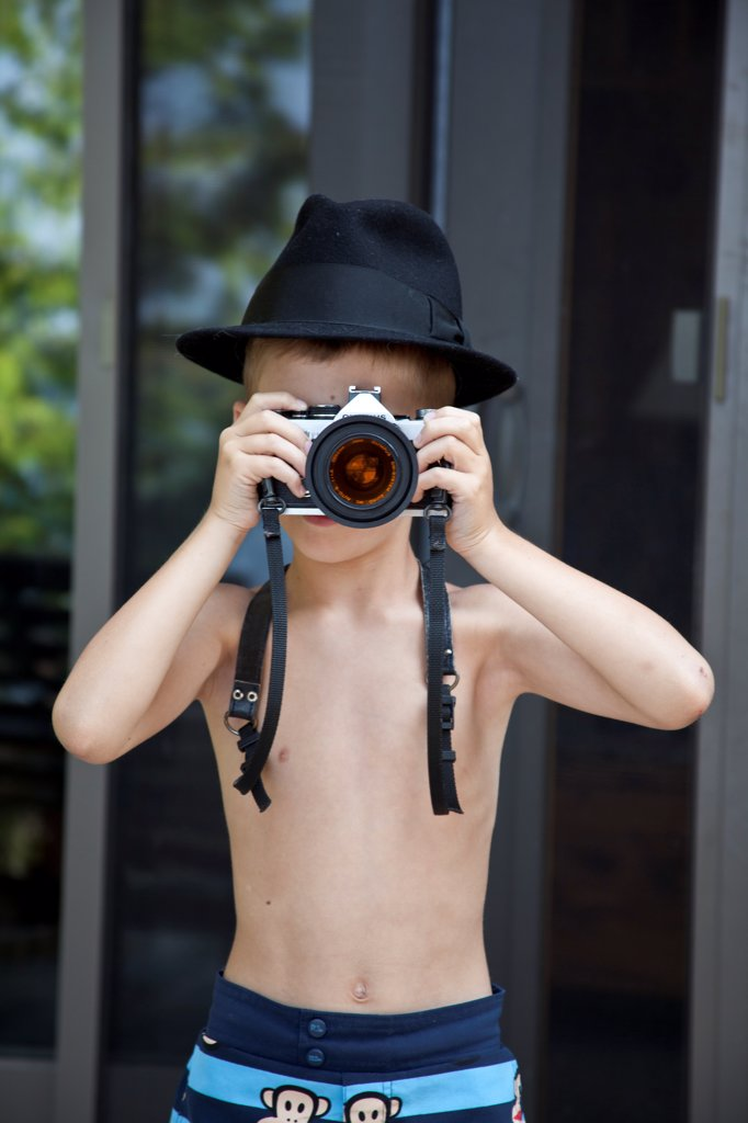 Stock Photo: 1838-14378 Young Boy Wearing Fedora Hat Taking Picture With Camera