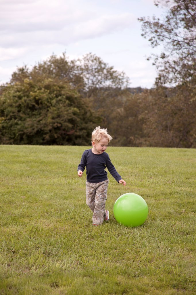 Stock Photo: 1838-14409 Young Boy Playing With Large Green Ball in Field