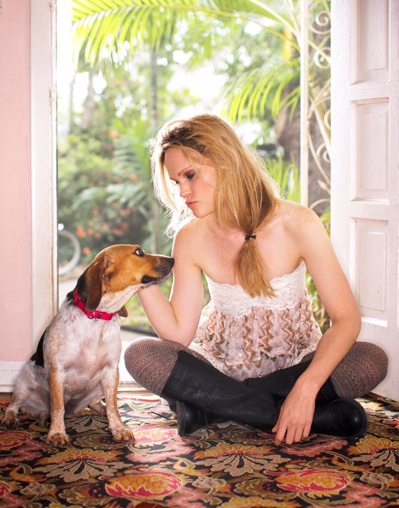 Stock Photo: 1838-14429 Young Woman and Dog Sitting in Front of Open Door