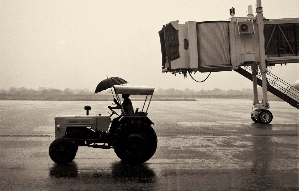 Stock Photo: 1838-14437 Man on Tractor Holding Umbrella at Airport