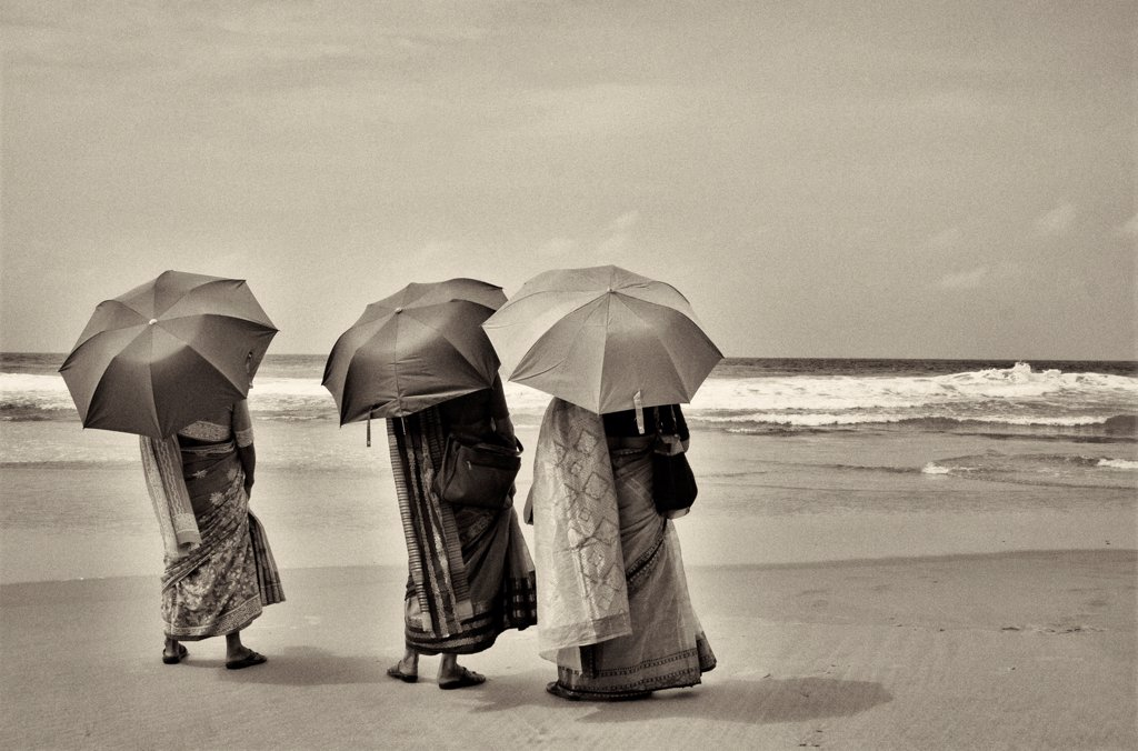 Stock Photo: 1838-14442 Three Women in Traditional Clothes on Beach With Umbrellas, Rear View, India