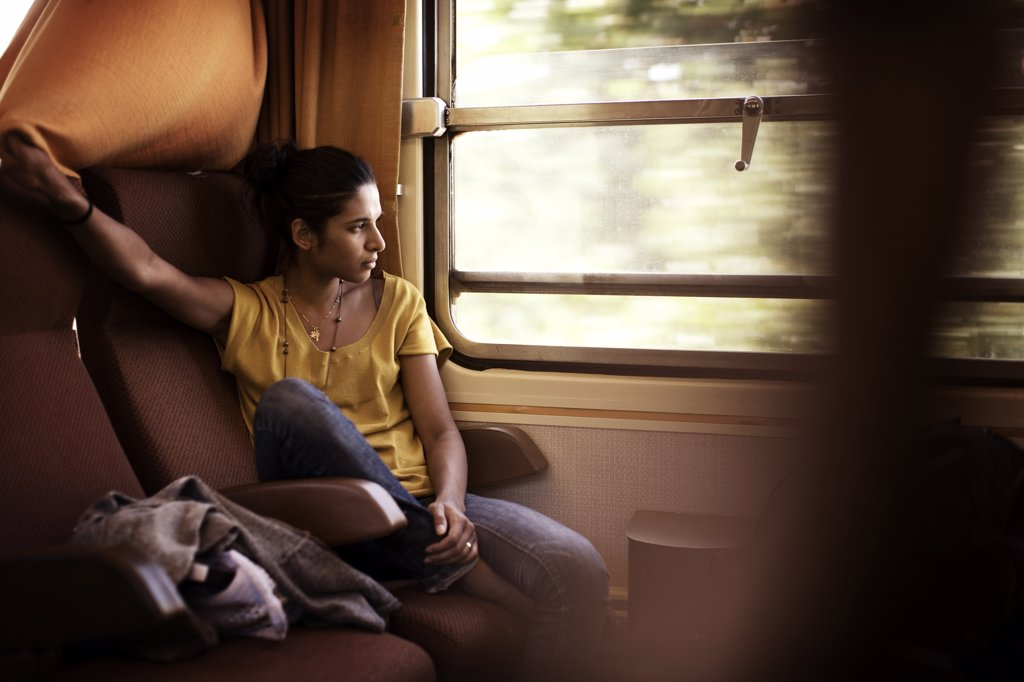 Stock Photo: 1838-7162 Young Reflective Woman sitting Inside Train