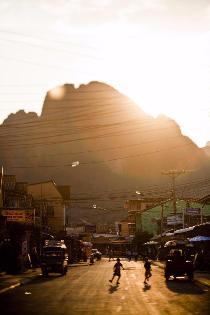 Stock Photo: 1838-7794 Sun Setting over Street Scene in Vang Vien, Laos