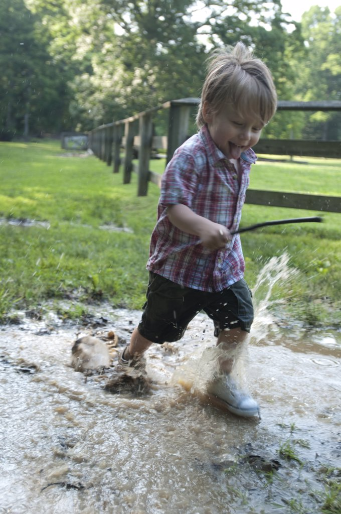 Stock Photo: 1838-9360 Smiling Young Boy Running Through Puddle and Carrying Stick
