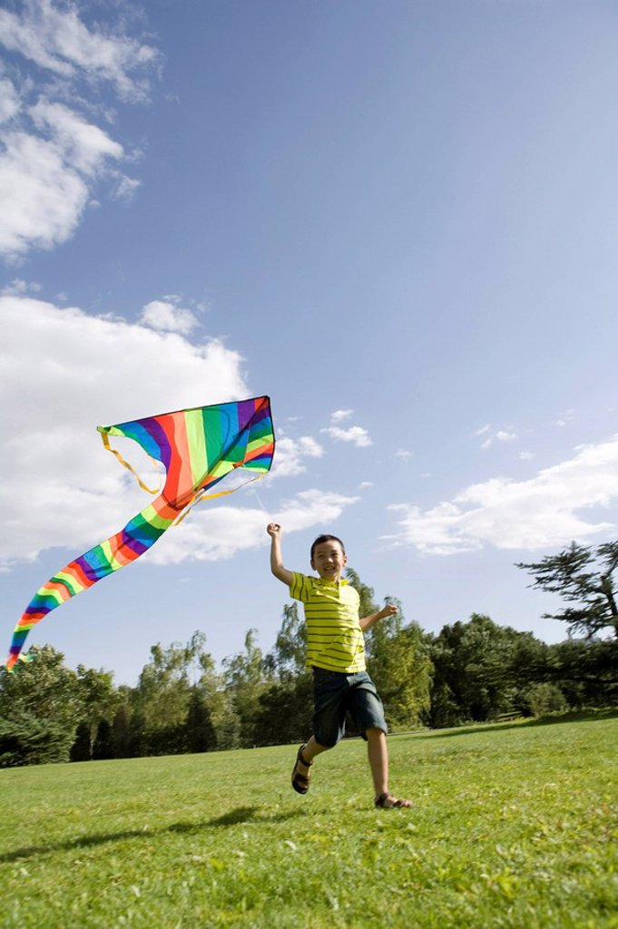 Young boy running with kite outdoors : Stock Photo