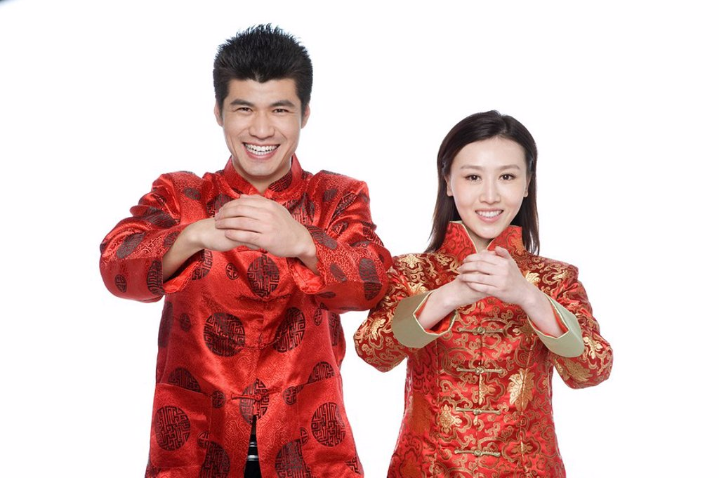 Young couple in Chinese traditional clothes giving best wishes : Stock Photo