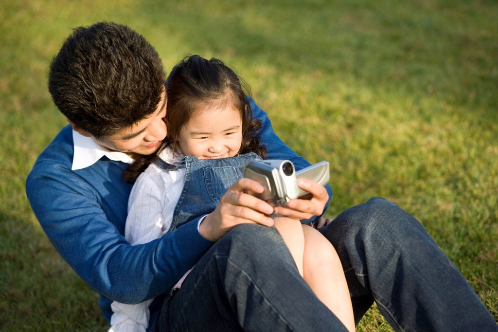 Father and daughter making a home video at the park : Stock Photo
