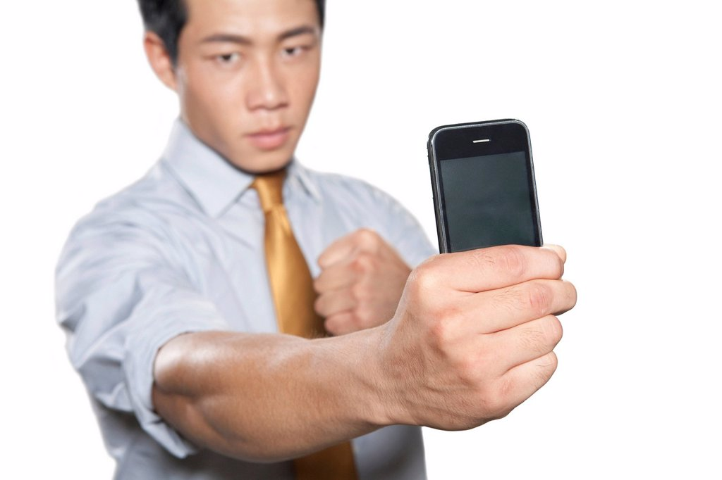 Businessman holding iPhone : Stock Photo