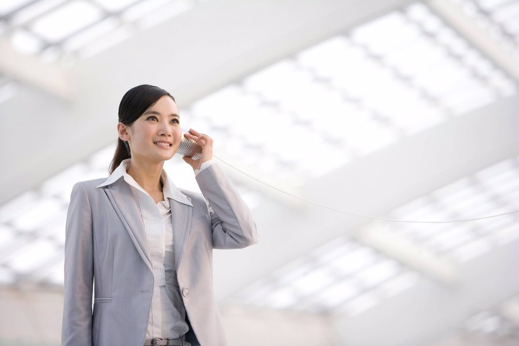 Businesswoman using tin can phone : Stock Photo