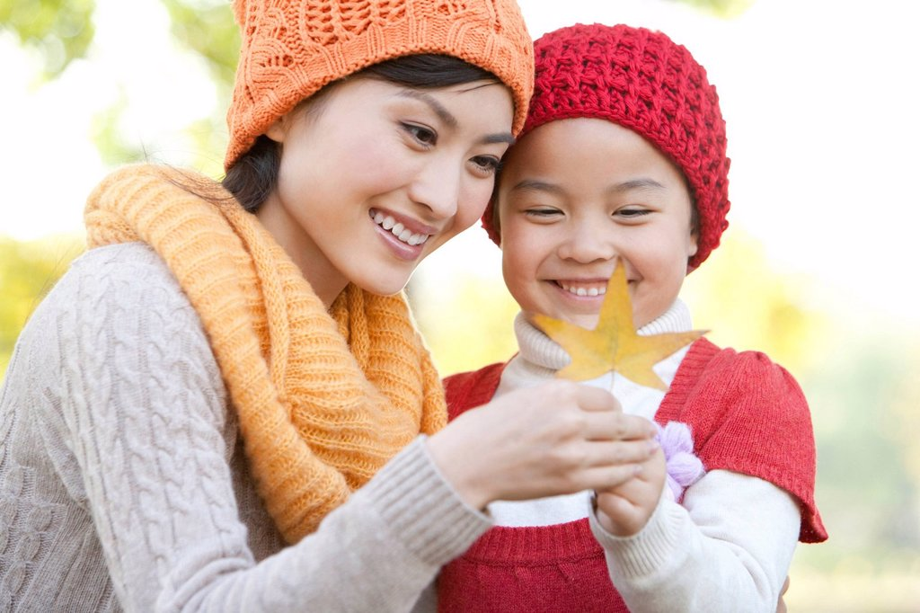 Stock Photo: 1839R-12816 Mother and Daughter in a Park Looking at a Maple Leaf