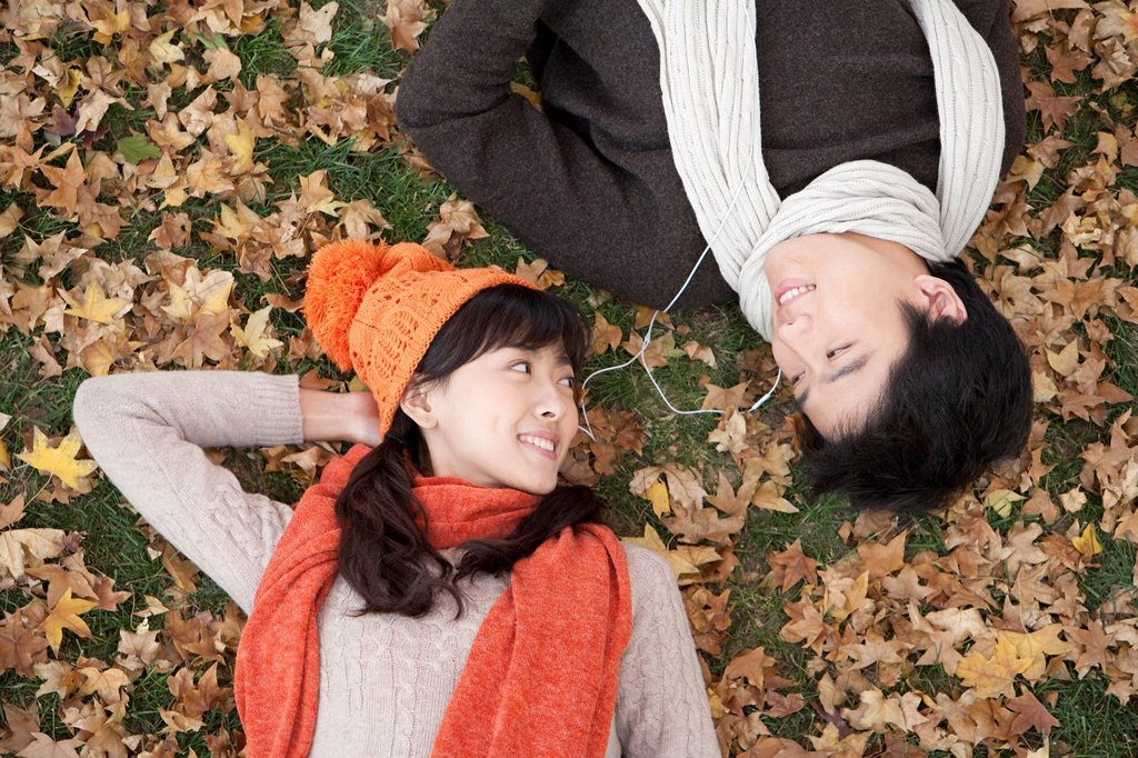 Young Couple Lying Amonst Maple Leaves Listening to MP3 Player : Stock Photo