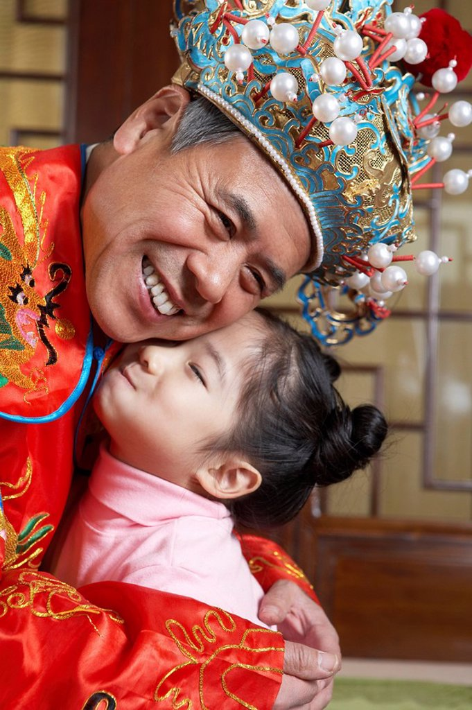 Grandfather In Traditional Costume Hugging His Granddaughter : Stock Photo