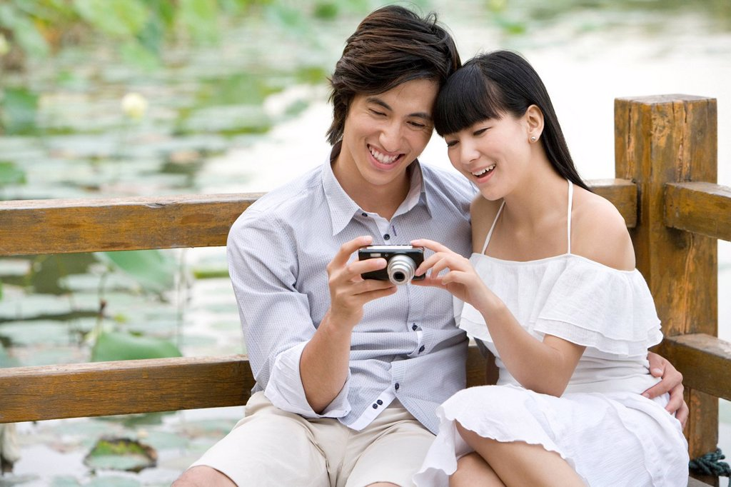 Young couple using digital camera outdoors : Stock Photo
