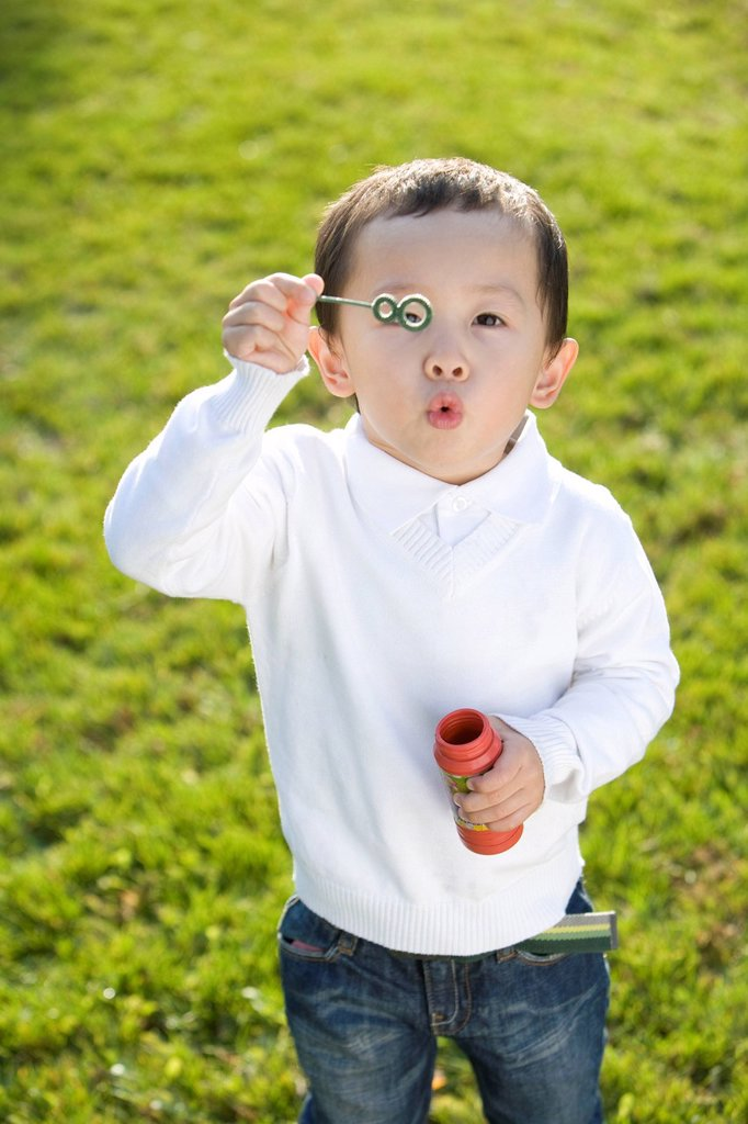 Stock Photo: 1839R-14329 Little boy blowing bubbles