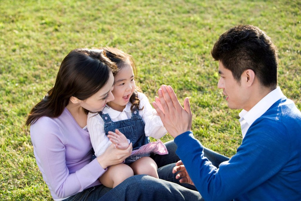 Stock Photo: 1839R-14376 Young family playing in the park