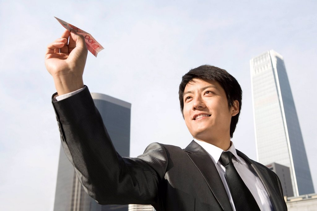 Businessman Flying RMB Paper Airplane : Stock Photo