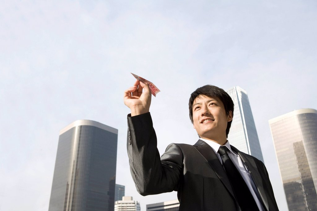 Stock Photo: 1839R-15153 Businessman Flying RMB Paper Airplane