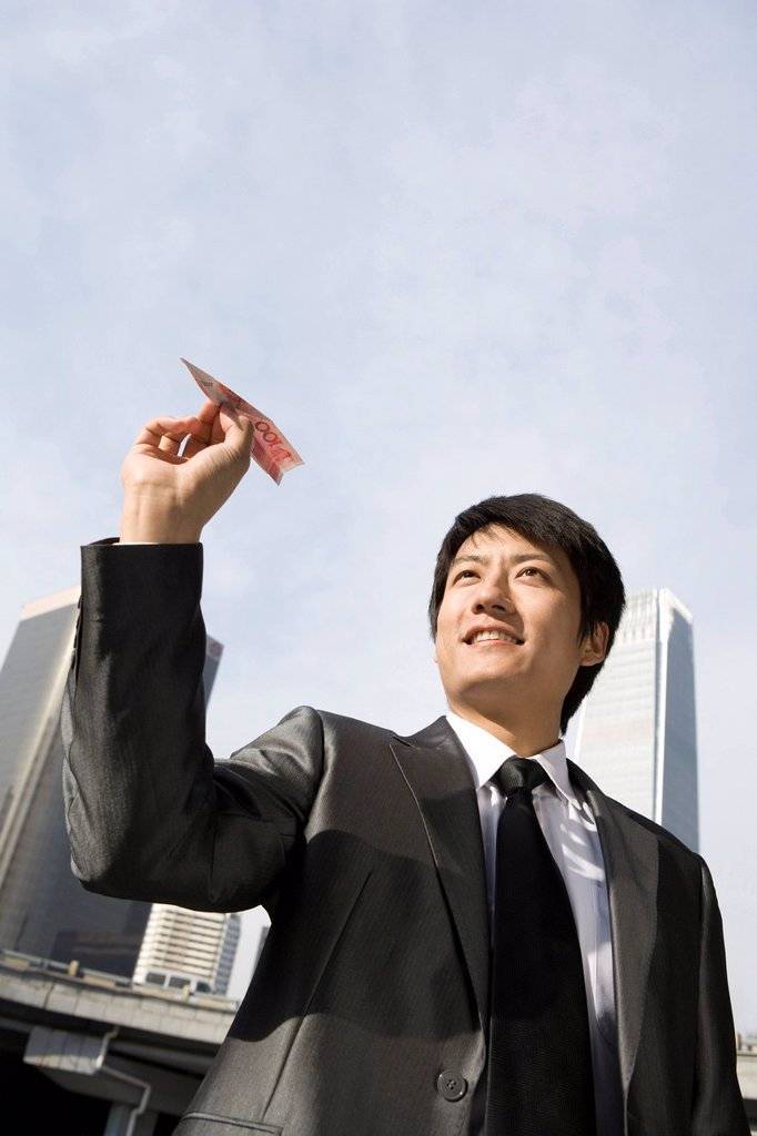Stock Photo: 1839R-15154 Businessman Flying RMB Paper Airplane
