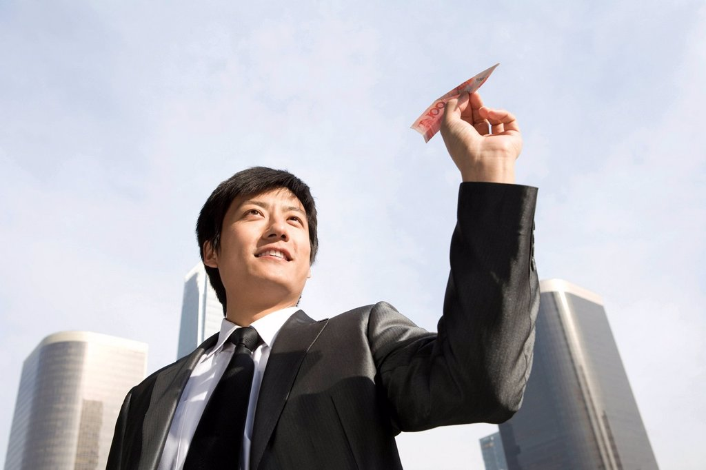 Stock Photo: 1839R-15155 Businessman Flying RMB Paper Airplane