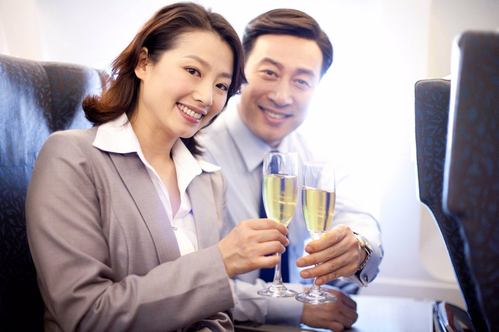 Stock Photo: 1839R-16570 Businesspeople toasting champagne on the plane