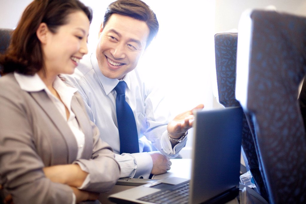 Businesspeople working on the plane : Stock Photo