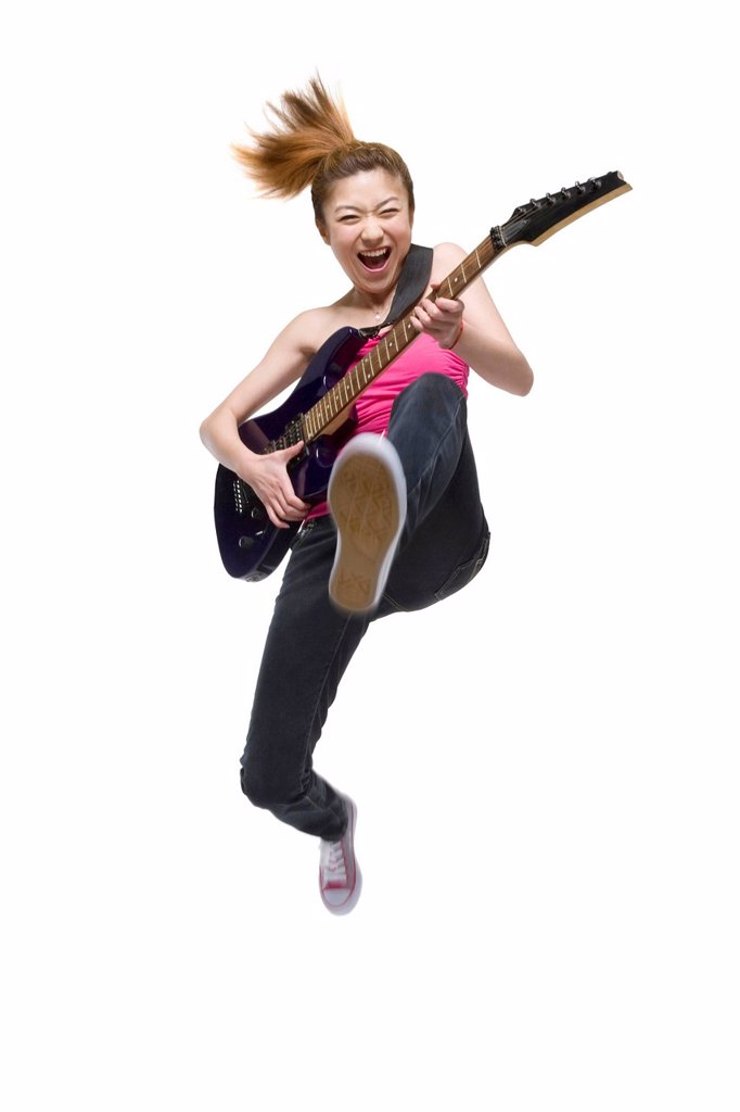 Stock Photo: 1839R-16735 Young woman playing an electric guitar