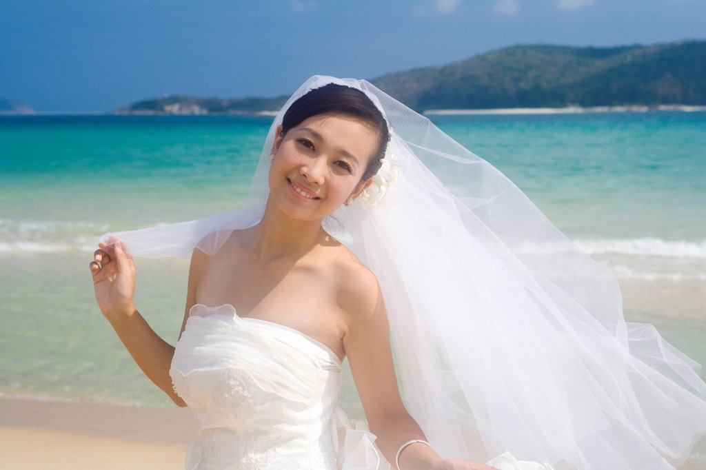 Stock Photo: 1839R-16851 Bride in a veil on the beach