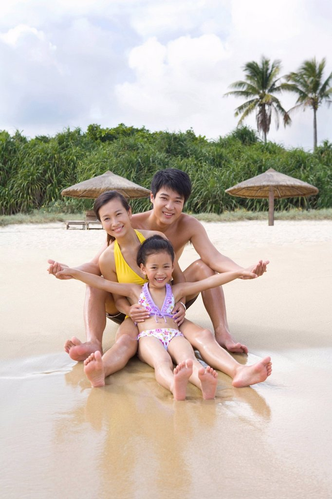 Portrait of a young family at the beach : Stock Photo