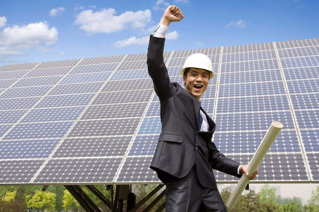 Portrait of an engineer in front of solar panels : Stock Photo