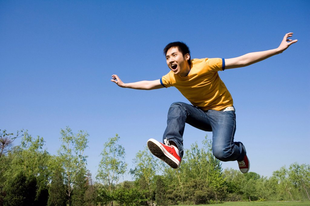 Stock Photo: 1839R-17611 Young man jumping in air at park