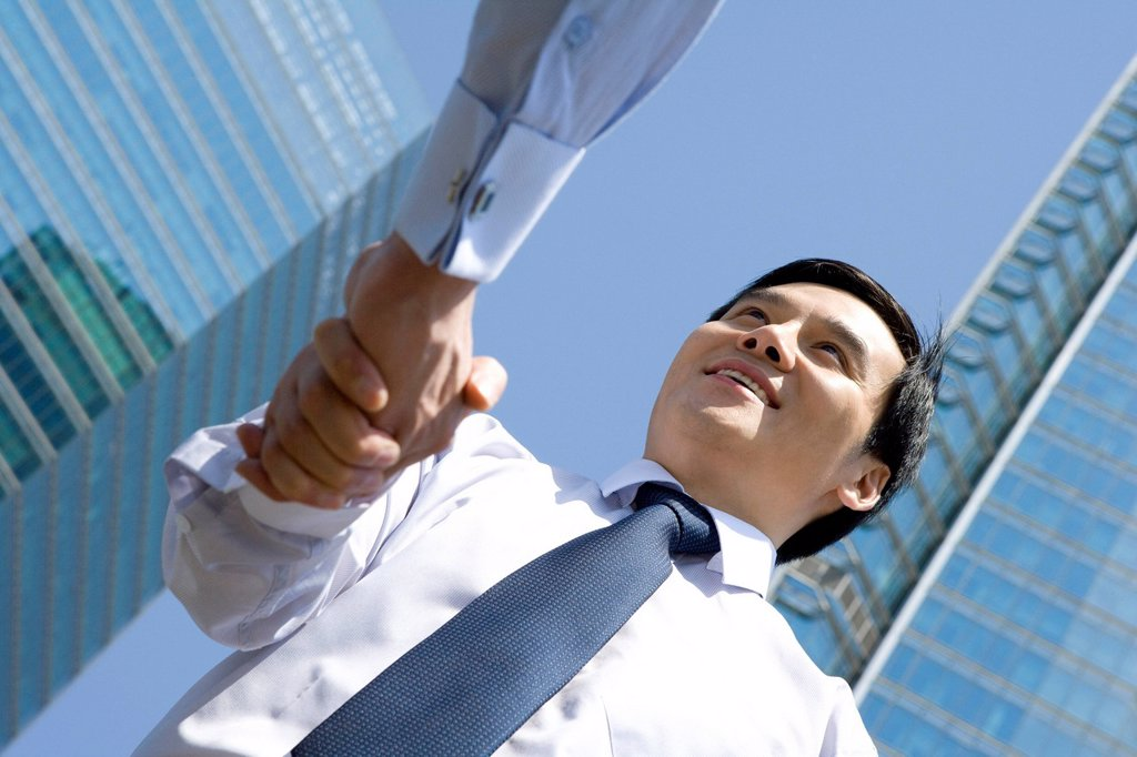 Stock Photo: 1839R-17843 Businessman shaking hands in an urban scene