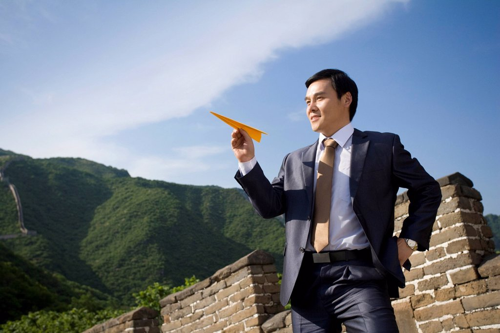 Stock Photo: 1839R-17923 Businessman on the Great Wall holding paper airplane