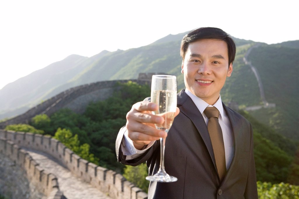 Stock Photo: 1839R-17959 Businessman having champagne on the Great Wall