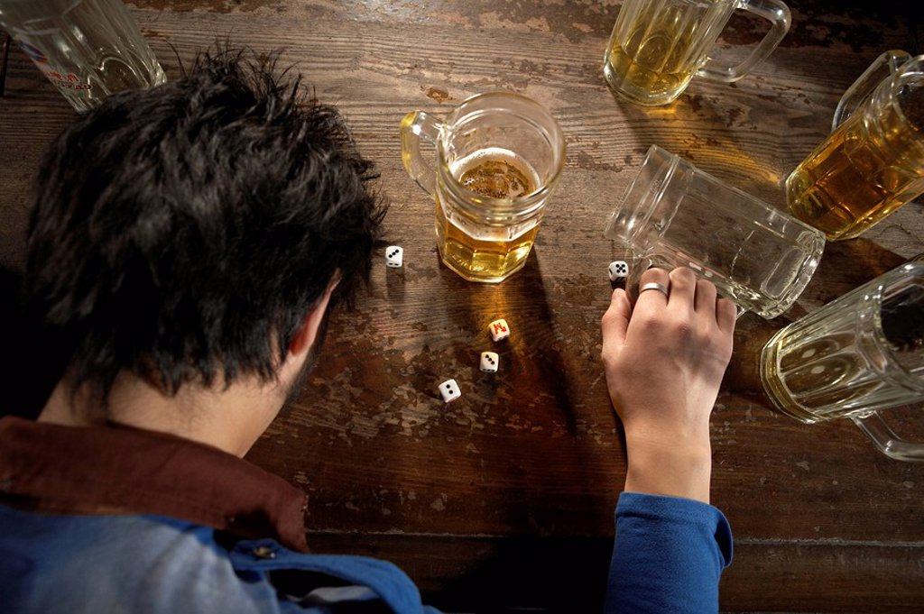 Stock Photo: 1839R-1820 Tired Young Man Sitting At Bar