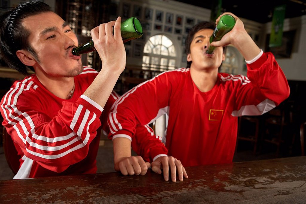 Sport Enthusiasts Drinking At Bar : Stock Photo