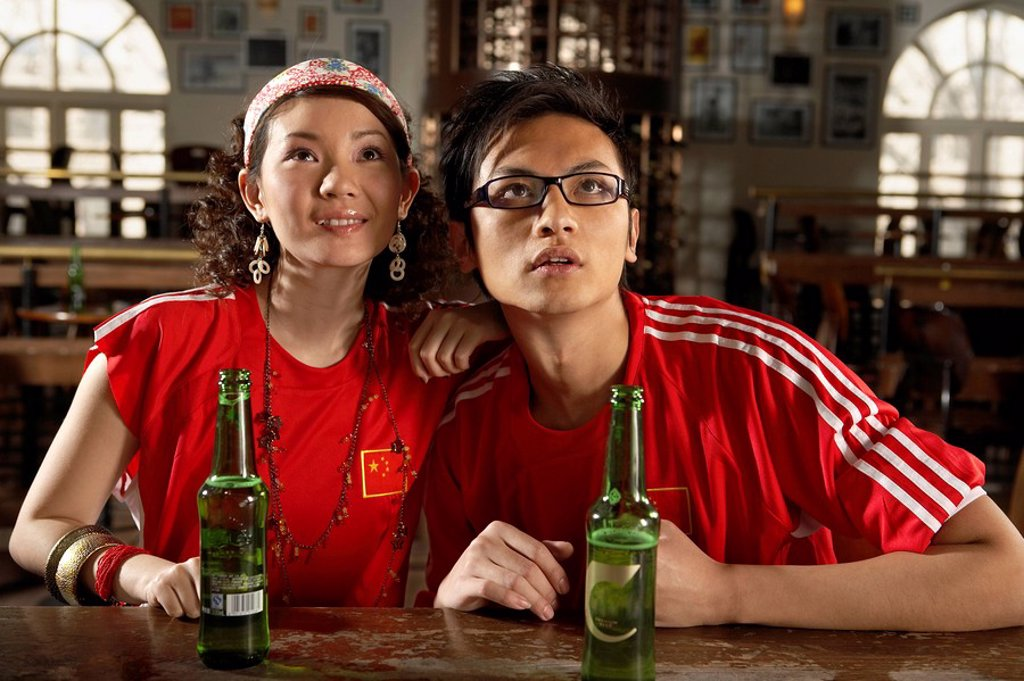 Sports Enthusiasts Watching Game In Bar : Stock Photo