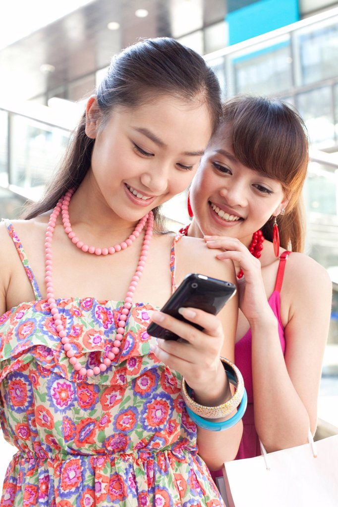 Two Young Women Looking at Phone : Stock Photo